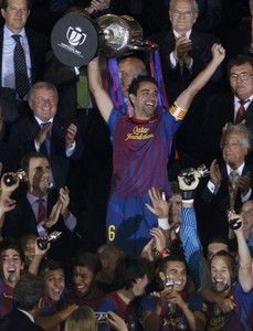 Barcelona\'s Xavi Hernandez lifts up the Spanish King\'s Cup trophy next to Spain\'s Crown Prince Felipe (L) after winning their final soccer match against Athletic Bilbao at the Vicente Calderon stadium in Madrid, May 25, 2012. REUTERS/Sergio Perez (SPAIN - Tags: SPORT SOCCER)