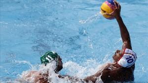 Francisco Fernández (d) pugna con el sudafricano Nicholas Molyneux durante el partido de la fase preliminar de waterpolo