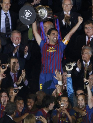 Barcelona\'s Xavi lifts up the Spanish King\'s Cup trophy after winning their final soccer match against Athletic Bilbao in Madrid