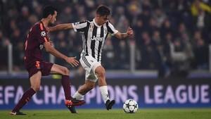 Una acción del partido entre la Juventus y el FC Barcelona. Busquets sale al paso ante Dybala