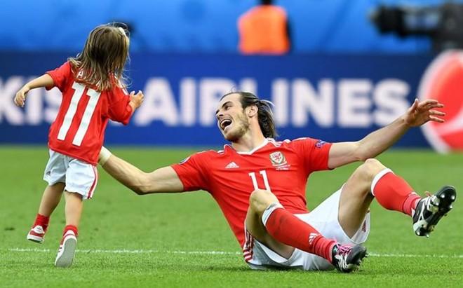 Bale, jugando con su hija sobre el c�sped del Parc des Princes