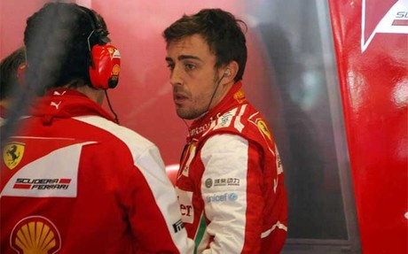 Fernando Alonso conversa con sus mecánicos en el boxe de Ferrari