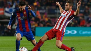El centrocampista atlético pugnando con Messi