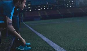 Neymar Junior se ata las botas durante un anuncio promocional de Nike
