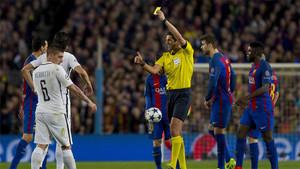 El árbitro muestra la amarilla que sanciona a Busquets