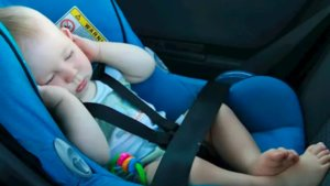 Bebé durmiendo en la sillita del coche.