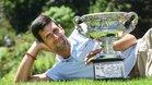 Novak Djokovic de Serbia posa para fotografiarse con el trofeo del campeonato en el Real Jardín Botánico de Melbourne.