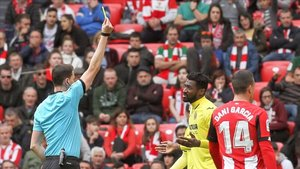 El árbitro David Medié muestra la tarjeta amarilla al centrocampista Zambo Anguissa