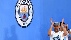 Pep Guardiola junto al escudo del City