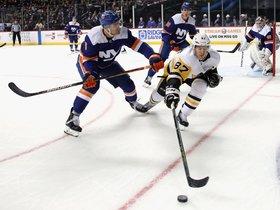 Sidney Crosby # 87 de los Pittsburgh Penguins lleva el disco contra Ryan Pulock # 6 de los New York Islanders en el Barclays Center.