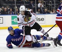 Brady Skjei # 76 de los New York Rangers derrota a Patrick Kane # 88 de los Chicago Blackhawks durante el primer período en el Madison Square Garden.