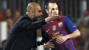 Iniesta escucha las indicaciones de Pep Guardiola en un partido