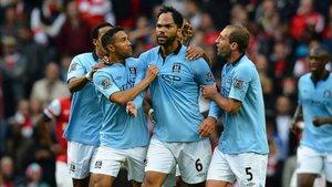Joleon Lescott, celebra con sus compañeros de equipo después de marcar gol en el partido de fútbol de la Premier League inglesa entre el Manchester City y el Arsenal en 2012.