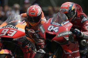 El piloto español del equipo Repsol Honda Marc Márquez (izq.) Y el piloto italiano de Mission Winnow Ducati Andrea Dovizioso montan sus motos durante la carrera del Gran Premio de Moto GP de Austria en Spielberg.