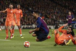 Jason Denayer del Olympique de Lyon comete falta sobre Luís Suárez, durante el partido de vuelta de los octavos de final de la Liga de Campeones que FC Barcelona y Olympique de Lyon juegan esta noche en el Camp Nou, en Barcelona.