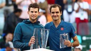 Thiem y Federer posando con los trofeos