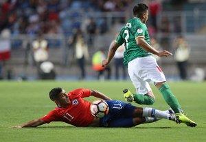 John Garcia (L) de Bolivia compite por el balón contra Matias Marin (L) de Chile durante su partido de fútbol sudamericano Sub-20 en el estadio El Teniente en Rancagua.