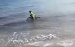 Un ciclista se mete en el mar con la bicicleta para evitar la multa de la policia (ES)