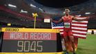 Eaton posa junto al marcador que registra su nuevo récord mundial