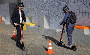 Dos personas prueban los patinetes eléctricos de Seat en la Smart City Expo de Barcelona.