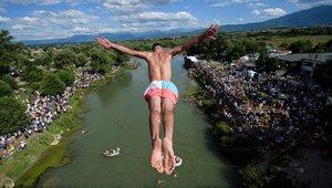 Un buzo salta desde el puente de 22 metros de altura Ura e Shenjte, como señal de protesta después de que la policía cancelara la 70ª competencia anual tradicional de buceo de altura en el puente, cerca de la ciudad de Gjakov.