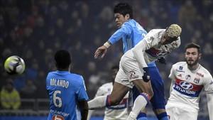 El delantero del Lyon Mariano cabecea un balón en presencia del defensa del Marsella Hiroki Sakai