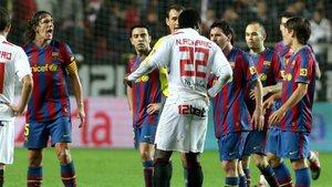 Los blaugrana Carles Puyol, Xavi Hernández, Leo Messi, Andrés Iniesta y Bojan Krkic discuten con el árbitro Clos Gómez y con el sevillista Romaric en el Sevilla-Barça de la Copa 2009/10