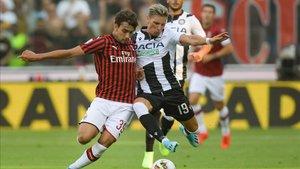 Disputa de un balón en el encuentro entre el Udinese y el Milán.
