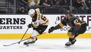 Brad Marchand # 63 de los Boston Bruins pasa el disco detrás de él bajo la presión de Shea Theodore # 27 de Vegas Golden Knights en el primer período de su juego en el T-Mobile Arena en Las Vegas, Nevada.