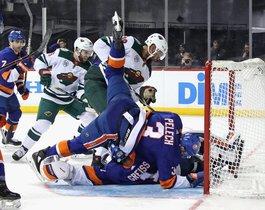 Adam Pelech # 3 y Thomas Greiss # 1 de los New York Islanders se defienden contra Jordan Greenway # 18 del Minnesota Wild durante el tercer período en el Barclays Center.