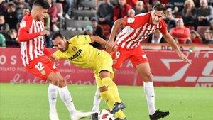 Cazorla trata de escaparse de la presión de dos jugadores rivales.