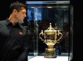 El exjugador de los All Blacks Dan Carter mira la Webb Ellis Cup, el trofeo para el ganador del Mundial de Rugby, que es exhibido en Tokyo de cara al Mundial del 2019