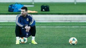 Leo Messi, sentado sobre el balón durante el entrenamiento