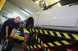 Un mecánico trabaja en un coche en un taller de Barcelona.