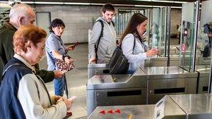 Unos usuarios del metro validan sus billetes, esta mañana