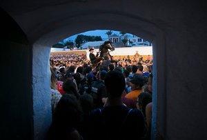Una cabalgata entre la multitud durante los Jocs des Pla, juegos ecuestres celebrados en el puerto lleno de gente durante el tradicional festival de Sant Joan (San Juan) en la ciudad de Ciutadella, en la isla balear de Menorca, el día de San Juan.
