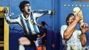 Un hombre y su hijo rinden homenaje junto a un mural que representa a la leyenda del fútbol argentino Diego Maradona en el barrio de La Boca, en Buenos Aires