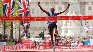 Wanjiru alza los brazos delante del Palacio de Buckingham