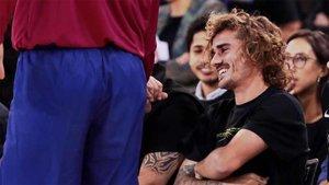 Griezmann sonríe sentado junto al banquillo que lidera Pesic