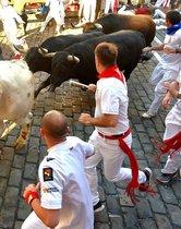 Los participantes corren junto a los toros Victoriano del Río Cortés en la tercera carrera de los San Fermines en Pamplona, norte de España.