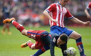 El jugador del Atlético VIetto cae ante Mere, del Sporting, en El Molinón