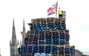 Los constructores de hogueras completan su estructura cerca del muro de la paz en el oeste de Belfast, Irlanda del Norte, antes de las tradicionales hogueras de la 11ª noche. - La Undécima Noche se refiere a la noche antes del 12 de julio.