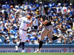 Justin Turner # 10 de los Dodgers de Los Angeles realiza una atrapada para terminar la tercera entrada frente a Ryan McMahon # 24 de los Colorado Rockies en el Dodger Stadium en Los Angeles, California.