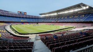 Las gradas del Camp Nou, vacías mientras los jugadores realizan los ejercicios de calentamiento