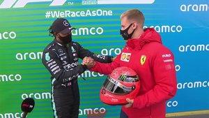 Mick Schumacher en el momento que le hace entrega del casco a Lewis Hamilton
