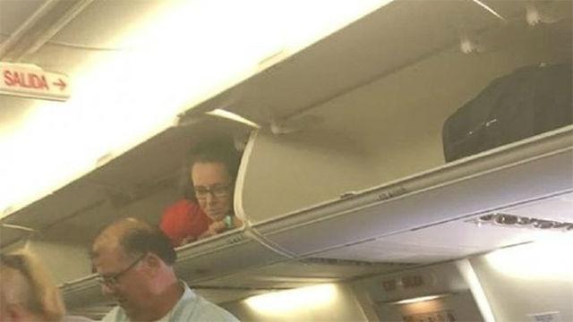 Una azafata de vuelo se esconde en una cabina de maletas