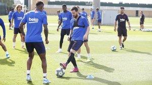 Leo Messi, en primer plano, y Ousmane Dembélé, detrás, se incorporaron al grupo en el entrenamiento del Barça
