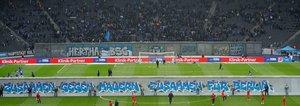 Una vista general muestra a los equipos calentando a ambos lados de una maqueta del antiguo Muro de Berlín con la inscripción Juntos contra los Muros, junto con Berlín de pie en el campo antes del comienzo del partido de fútbol de la primera divisi