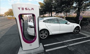 Tesla Model S 8Unidad del vehículo junto a una estación de carga.