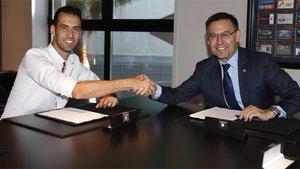 Sergio Busquets y el presidente Josep Maria Bartomeu tras la renovación de contrato del mediocentro del FC Barcelona